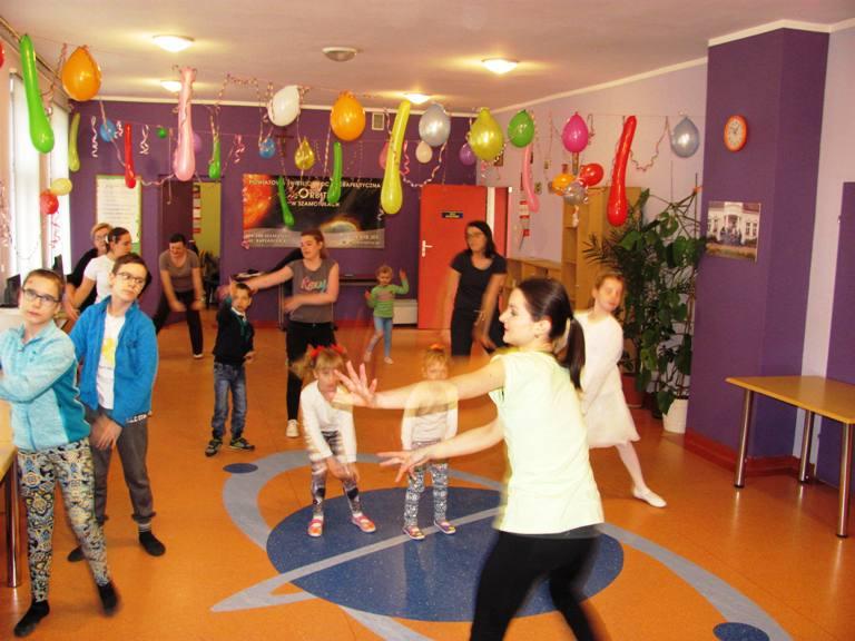 Dzieci tańczące z dorosłymi na sali gimnastycznej.
