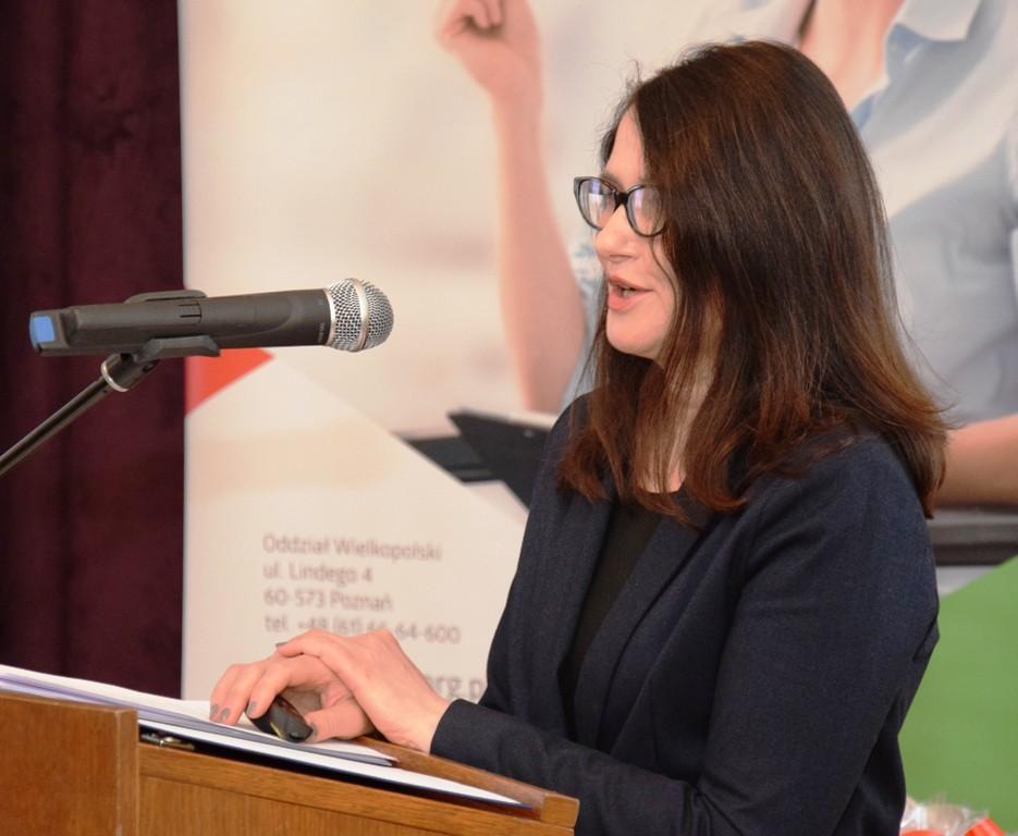 Prezes PFRON Dorota Habich stojąca przy mównicy drewnianej.